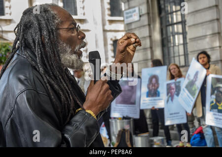 London, UK. 16th August 2018. Protesters hold a vigil outside the South African High Commission in Trafalgar Square on the 6th anniversary of the massacre when 34 striking miners were shot dead by South African police at Lonmin's Marikana platinum mine. After speeches about the event, the names of the 34 victims were read and large photographs of them put on the front of the embassy along with flowere. Although evidence against the police was clear, 19 strikers were changed with murder and others imprisoned for other offences. Credit: Peter Marshall/Alamy Live News - Stock Image