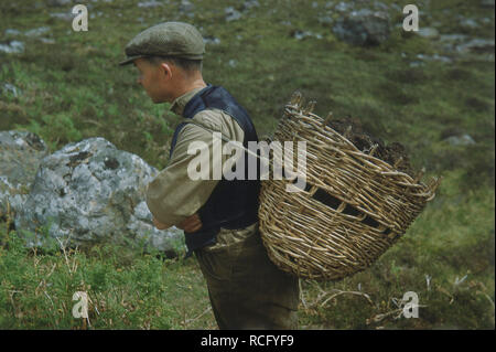1960s, historical, man with cap carrying a wicker basket of peat on his back, Ireland, UK. - Stock Image