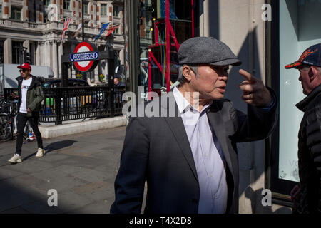 Passers-by walk outside the Harvey Nichols department store on the corner of Knightsbridge and Sloane Street, on 11th April 2019, in London, England. - Stock Image