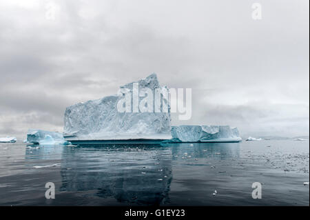 Floating blue ice, reflection and moody sky Cierva Cove Antarctic Peninsula Antarctica - Stock Image