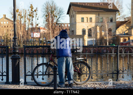 Man with bicycle leaning on a railing on the Watlaw river, Gadansk, Poland - Stock Image