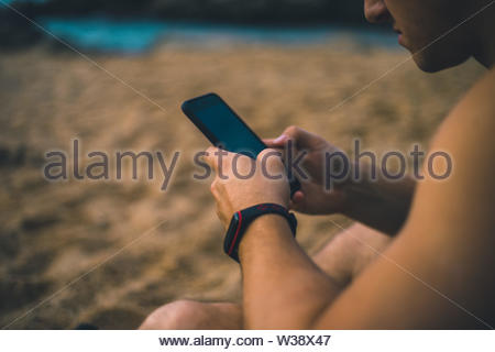 Boy with a smart phone on the beach - Stock Image
