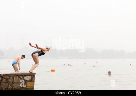 Two old ladies diving in the lake at Shuishang Park, Tianjin, China. - Stock Image