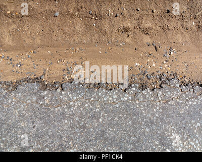 Close up of section of tarmac road breaking down into soil edge - Stock Image