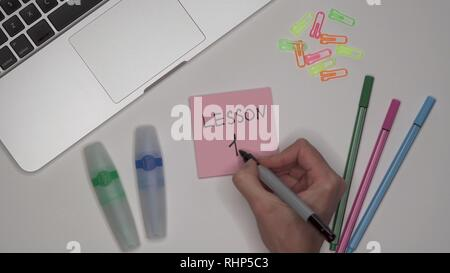 LESSON 1 written on notepad. Laptop and stationery on the table. Close up - Stock Image