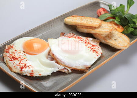 Two fried eggs with some bread and salad next to them - Stock Image