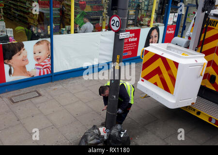 A workman attaches ties to a lamp post on the Walworth Road in the south London borough of Southwark, on 7th March 2019, in London, England. - Stock Image