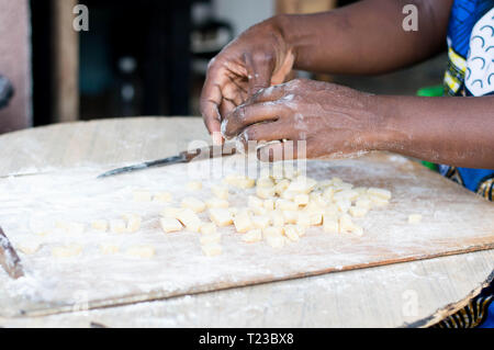 Close-up of female hands kneading flour on a board with natural light - Stock Image