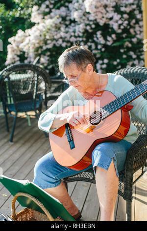 Senior woman playing guitar - Stock Image