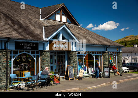 UK, Cumbria, Hawkshead, Hawkshead outdoor clothing shop and Naturally Hawkshead cafe with customer sat in sunshine at outside table - Stock Image