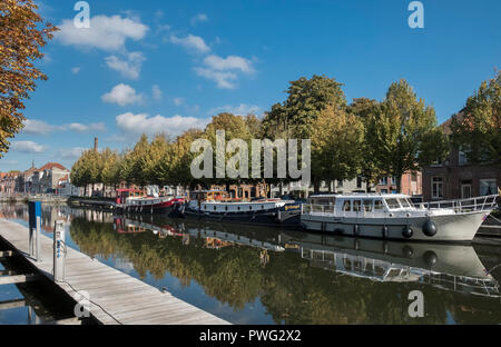Canal boats moored alongside residential housing in the historic city of Bruges, West Flanders, Belgium. - Stock Image