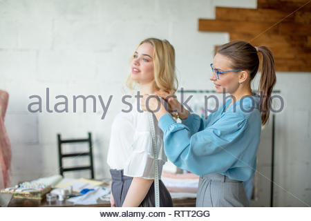 Female tailor measuring woman back to make custom made suit for blonde beautiful client in her dressmaker s studio . Garment industry, tailoring proce - Stock Image