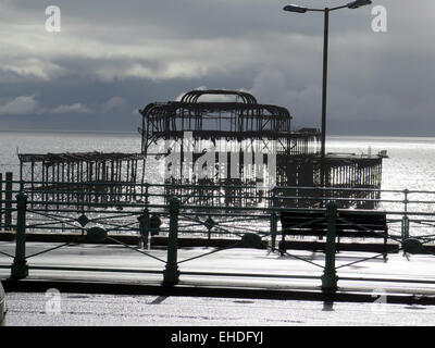 The Arson attacked ruin of the West Pier, Brighton designed by Eugenius Birch, seen across the promenade with decorative - Stock Image
