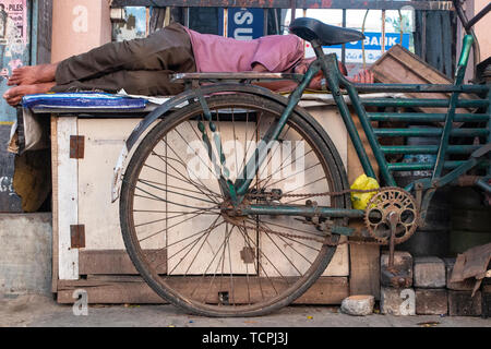 Poverty in Chennai, India, where a barefoot man sleeps on a bench - Stock Image