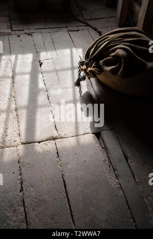 Sunlight casting shadows on the dusty old floor of the Charlecote Watermill with a sack of grain - Stock Image