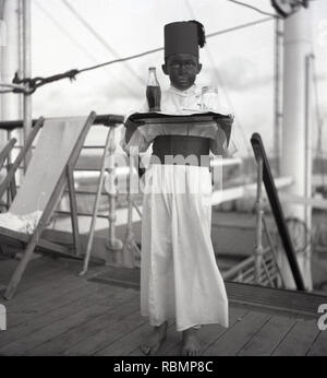 1950s, historical, Union-Castle Steamship, young boy in a fancy dress competition on the deck of a ship dressed in a costume as a foreign (egyptian) waiter and holding a tray with a soft drink bottle. - Stock Image