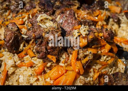 Rice pilaf, also known as plov or pilau, a national cuisine dish in Uzbekistan and other Central and South Asian countries, as well as in the Caucasus - Stock Image