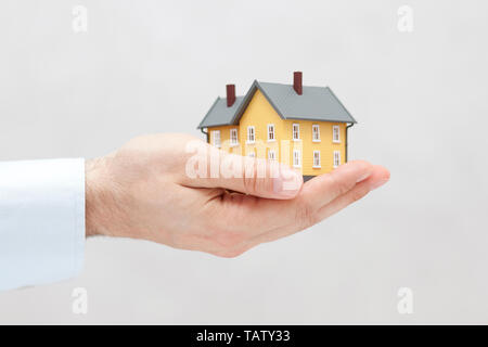 Small yellow house miniature in hand - Stock Image