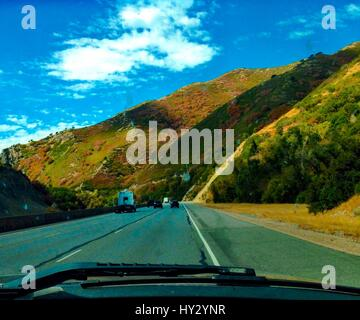 Car On Road Amidst Mountains Against Sky - Stock Image
