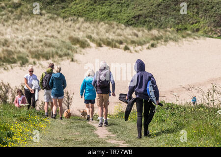 Holidaymakers walking on the footpath leading to the secluded Polly Porth Joke in Newquay in Cornwall - Stock Image