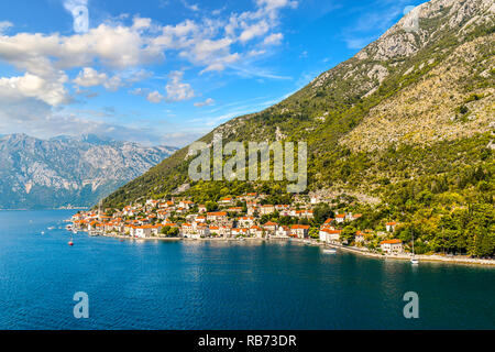 View of the the medieval village of Perast, including the St. Nikola Church tower, along the coast of the Bay of Kotor, Montenegro. - Stock Image