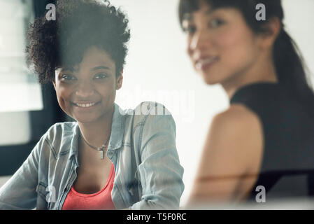 Smiling businesswomen sitting in office - Stock Image