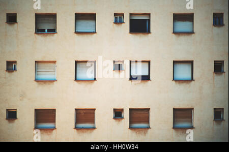 Beige facade of residential building in Barcelona with regular pattern of windows of different size, streaks of - Stock Image