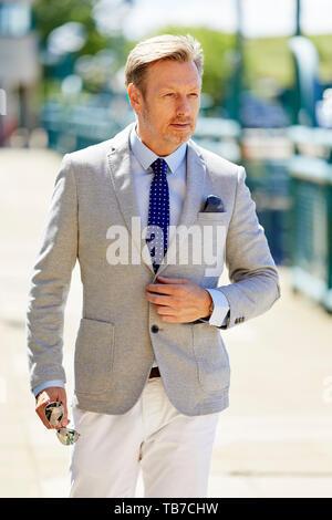 Businessman walking to work - Stock Image