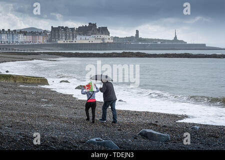 Aberystwyth Wales UK, Saturday 15th June 2019  UK Weather: A couple have the beach to themselves on a grey and wet afternoon at the seaside in Aberystwyth , west wales, as the dreary wet and very unsesonal June 'summer' weather continues its hold on the country  photo credit Keith Morris / Alamy Live News - Stock Image
