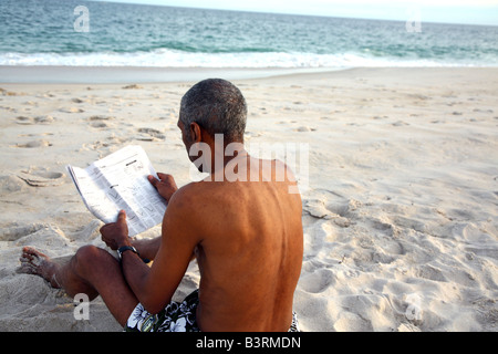 Mature African American man reading on a beach - Stock Image