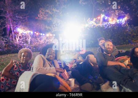 Happy friends enjoying movie in backyard - Stock Image