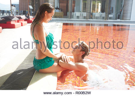 Young couple in orange swimming pool - Stock Image