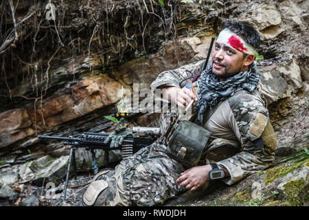 Wounded Army ranger machine gunner in the mountains. - Stock Image