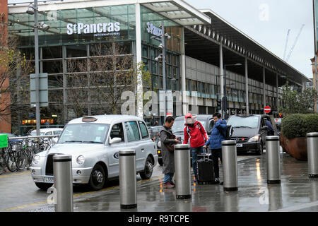 View passengers & luggage getting out of taxi at St Pancras Station building Pancras Road at Kings Cross & tourist Big Bus London UK  KATHY DEWITT - Stock Image