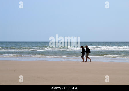 A man and woman walking barefoot along a deserted beach in Wales with waves breaking in the background. - Stock Image