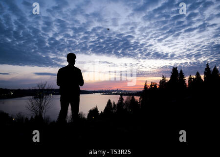 Silhouette of a man controlling a drone that is in the background - Stock Image