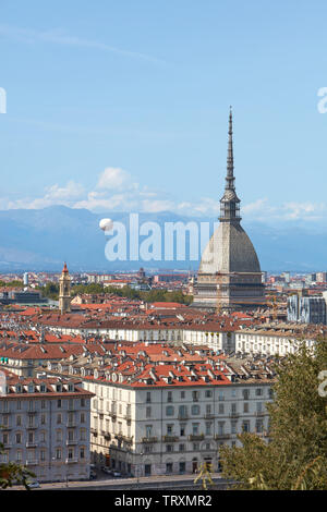 Mole Antonelliana tower and hot air balloon over Turin rooftops in a sunny summer day in Italy - Stock Image