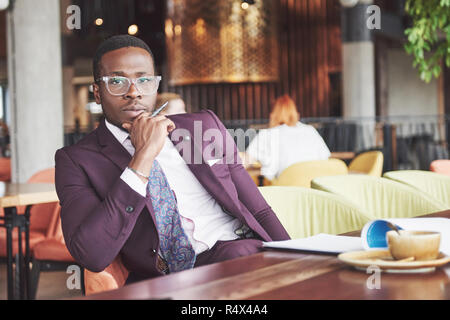A young businessman signs a contract in a conference room - Stock Image