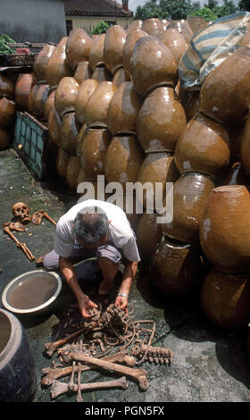 A Man removes bones from a earthenware earthenware jar and washes them in an ancestral worship ritual conducted annually in some parts of China - Stock Image
