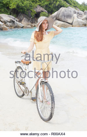 Young woman wearing yellow dress with bicycle on beach - Stock Image