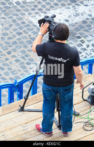 A telesafor television camerman videoing an event - Stock Image