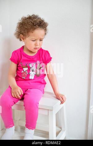 Sad girl sitting on stool - Stock Image