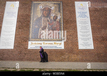 A priest passes a banner, showing a picture of the Black Madonna, during the celebration of the assumption of Mary in August, Poland in 2018. - Stock Image