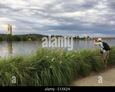 Tourist photographing Canberra's Lake Burley Griffin and The Carillon - Stock Image