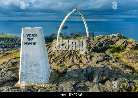 The trig point and replica whale bones on the summit of North Berwick Law, East Lothian, Scotland, UK - Stock Image