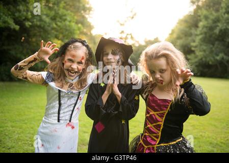 Three children dressed in costume for Halloween Night. - Stock Image