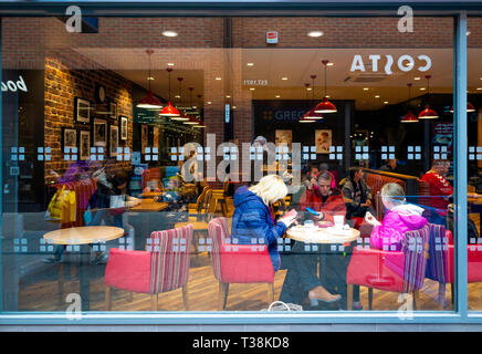 Coffee Shop reflections looking into a Greggs coffee shop window with a reflection of a Costa shop opposite with customers enjoying their refreshments - Stock Image