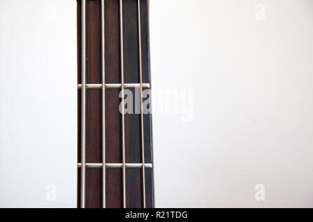 The neck of a bass guitar against white copy space - Stock Image