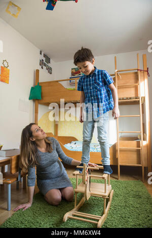 Boy balancing on rocking horse while pregnant mother is watching, Munich, Germany - Stock Image