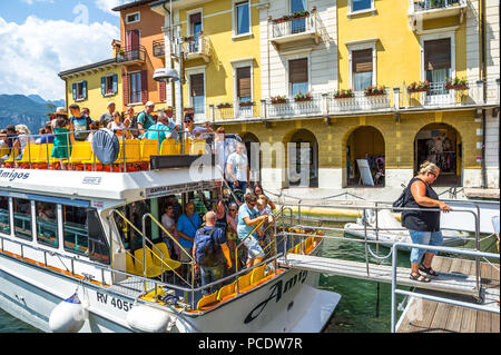Passengers leaving a small boat at Malcesine on Lake Garda. - Stock Image